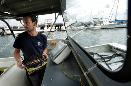 Frank Marino, an engineer with Sea Machines Robotics, uses a remote control belt pack to control a self-driving boat in Boston Harbor. Spurred on by the car industry's race to build driverless vehicles, maritime companies are taking advantage of technological breakthroughs and broader public acceptance of artificial intelligence to design tugboats, ferries and cargo vessels that won't need captains or crews, at least not on board