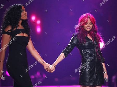 """Jordin Sparks, left, and Allison Iraheta perform at the """"American Idol"""" farewell season finale at the Dolby Theatre, in Los Angeles"""