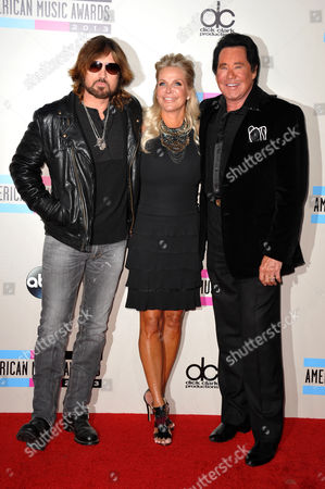 From left, Billy Ray Cyrus, Kathleen McCrone, and Wayne Newton arrive at the American Music Awards at the Nokia Theatre L.A. Live, in Los Angeles