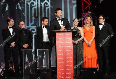 """Bradley Cooper, center, and from left, Shea Whigham, Paul Herman, Jeremy Renner, Amy Adams, Elisabeth Rohm and David O. Russell accept the ensemble performance award for """"American Hustle"""" at the Palm Springs International Film Festival Awards Gala at the Palm Springs Convention Center, in Palm Springs, Calif"""