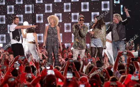 Pharrell Williams, second from left, and Little Big Town perform One Dance at the CMT Music Awards at the Bridgestone Arena, in Nashville, Tenn. From left are, Jimi Westbrook, Kimberly Roads Schlapman, Pharrell Williams, Karen Fairchild and Phillip Sweet