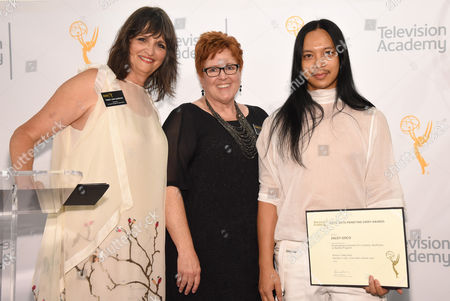 """The Television Academy's Terry Ann Gordon. from left, Sue Bub and Zaldy Goco poses with a plaque for his Emmy nomination for """"RuPaul's Drag Race Keeping it 100!"""" at the 10th Annual Art of Television Costume Design Exhibition opening at the FIDM Museum & Galleries on the Park, in Los Angeles"""