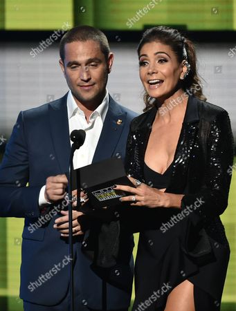 Michel Brown, left, and Patricia Manterola present the award for favorite urban band/duo/group at the Latin American Music Awards at the Dolby Theatre, in Los Angeles