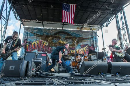 """From left, Dave Briggs, Tim """"Two Guns"""" Cord, Phil """"The Thrill"""" Snyder, and Dan """"Hitman"""" Cord of the band American Hitmen perform during the 32nd Love Ride at Castaic Lake, in Castaic, Calif"""