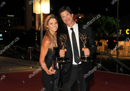 """Steven Levitan, right, and Krista Levitan pose with the awards for outstanding comedy series and outstanding directing in a comedy series for """"Modern Family"""" as they arrive at the 64th Primetime Emmy Awards Governors Ball, in Los Angeles"""