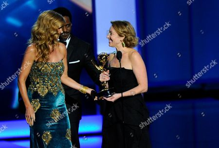 """From left, Connie Britton and Blair Underwood present the award for outstanding writing for a drama series to Sarah Bromell, who is accepting the award on behalf of her late husband Henry Bromell for hsi work on """"Homeland"""" at the 65th Primetime Emmy Awards at Nokia Theatre, in Los Angeles"""