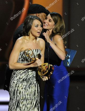 Tina Fey, right, is embraced by L L Cool J as Tracey Wigfield, left, accepts the award for outstanding writing for a comedy series for their work on 30 Rock at the 65th Primetime Emmy Awards at Nokia Theatre, in Los Angeles