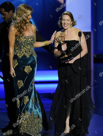 """Connie Britton, foreground left, and Blair Underwood, background left, present the award for outstanding writing for a drama series to Sarah Bromell on behalf of her late husband Henry Bromell's work on """"Homeland"""" at the 65th Primetime Emmy Awards at Nokia Theatre, in Los Angeles"""