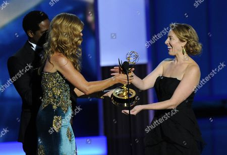 """Connie Britton, left, presents the award for outstanding writing for a drama series to Sarah Bromell on behalf of her late husband Henry Bromell's work on """"Homeland"""" at the 65th Primetime Emmy Awards at Nokia Theatre, in Los Angeles"""