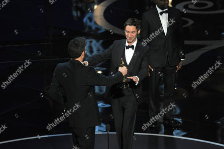 """Malik Bendjelloul accepts the award for best documentary feature for """"Searching for Sugar Man"""" from presenter Ben Affleck during the Oscars at the Dolby Theatre, in Los Angeles"""