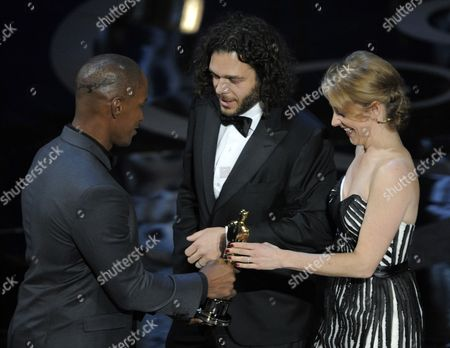 "Actor Jamie Foxx, left, presents the award for best documentary short to Sean Fine and Andrea Nix Fine for ""Inocente"" during the Oscars at the Dolby Theatre, in Los Angeles"