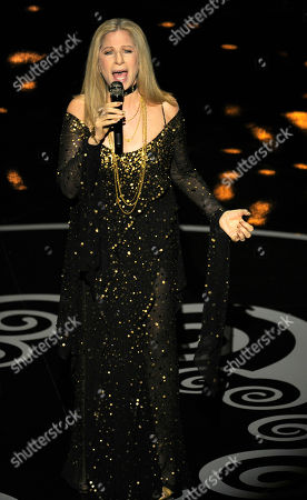 """Stock Image of Actress/singer Barbra Streisand performs """"The Way We Were"""" for the In Memoriam tribute during the Oscars at the Dolby Theatre, in Los Angeles. Pictured on the screen is the song's Oscar-winning composer, Marvin Hamlisch, who died in 2012"""