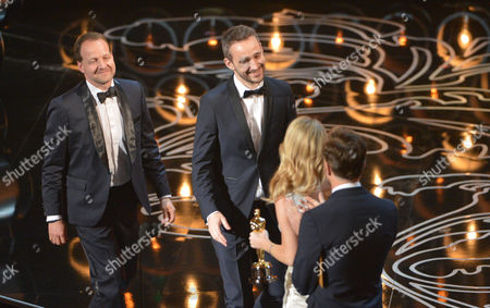 Kim Magnusson, left, and Anders Walter walk on stage to accept the award for best live action short film of the year for Helium during the Oscars at the Dolby Theatre, in Los Angeles