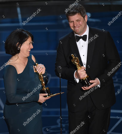 Anna Pinnock, left, and Adam Stockhausen accept the award for best production design for The Grand Budapest Hotel at the Oscars, at the Dolby Theatre in Los Angeles