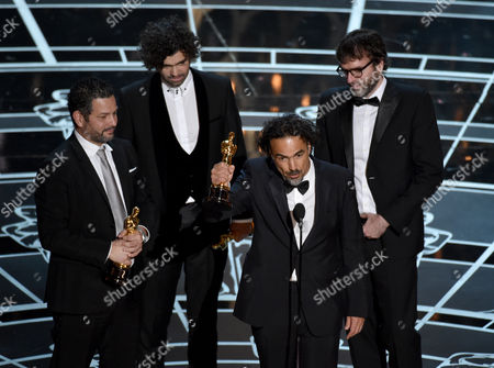 Alexander Dinelaris, from left, Armando Bo, Alejandro G. Inarritu and Nicolas Giacobone accept the award for the best original screenplay for Birdman or (The Unexpected Virtue of Ignorance) at the Oscars, at the Dolby Theatre in Los Angeles