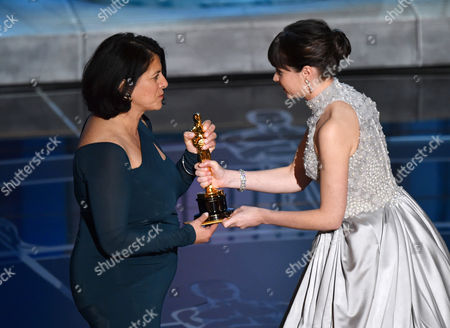 Felicity Jones, right, presents Anna Pinnock with the award for best production design for The Grand Budapest Hotel at the Oscars, at the Dolby Theatre in Los Angeles
