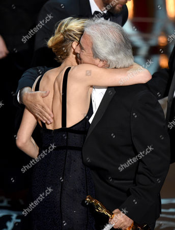 Sienna Miller, left, presents Alan Robert Murray with the award for best sound editing for American Sniper at the Oscars, at the Dolby Theatre in Los Angeles