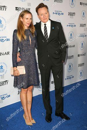 Liza Powel, left, and Conan O'Brien arrive at the Autism Speaks to LA Celebrity Chef Gala at Barker Hangar, in Santa Monica, Calif
