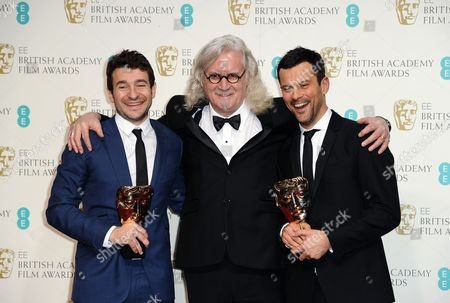 Director Bart Layton, left, and producer Dimitri Doganis, right, pose with their award for Outstanding Debut by a British Writer, Director or Producer with Billy Connolly at the BAFTA Film Awards at the Royal Opera House, in London