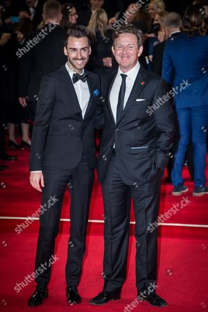 Tommy Tonge and John Logan pose for photographers upon arrival at the world premiere of the latest James Bond film, 'Spectre' in London
