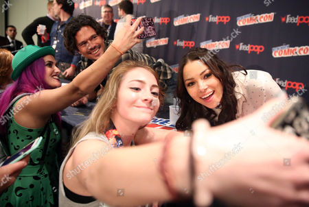"Jessica Parker Kennedy, right, and Luke Arnold take photos with fans after the panel for the STARZ Original Series ""Black Sails"" at New York Comic Con on in New York"