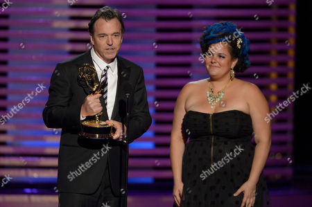 """Derek McLane, left, and Gloria Lambat accept the award for outstanding art direction for variety, nonfiction, reality or reality-competition for """"The Oscars"""" at the Television Academy's Creative Arts Emmy Awards at the Nokia Theater L.A. LIVE, in Los Angeles"""