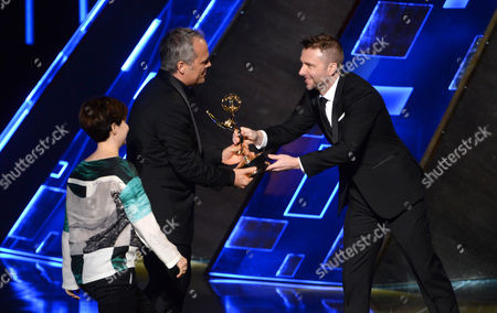 Stock Photo of Mathilde Bonnefoy, and from left, Dirk Wilutzky accept the award for exceptional merit in documentary filmmaking for their work on Citizenfour from Chris Hardwick at the Television Academy's Creative Arts Emmy Awards at Microsoft Theater, in Los Angeles