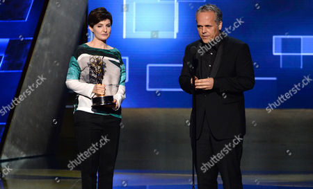 Stock Image of Mathilde Bonnefoy, left, and Dirk Wilutzky accept the award for exceptional merit in documentary filmmaking for their work on Citizenfour at the Television Academy's Creative Arts Emmy Awards at Microsoft Theater, in Los Angeles
