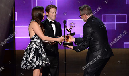 Mae Whitman, left, and Seth Green present Monte C. Haught with the award for outstanding hairstyling for a limited series or a movie for American Horror Story: Freak Show at the Television Academy's Creative Arts Emmy Awards at Microsoft Theater, in Los Angeles