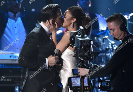 Cheyenne Jackson, left, and Alexandra Silber kiss after their performance at the 57th annual Grammy Awards, in Los Angeles