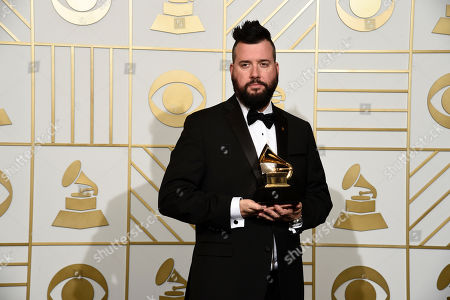 "Dave Aude poses in the press room with the award for best remixed recording, non-classical for ""Uptown Funk (Dave Aude Remix)"" at the 58th annual Grammy Awards at the Staples Center, in Los Angeles"