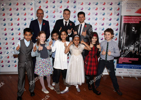 From left, Eric Fellner, CEO of Working Title Films, and show hosts Ben Willbond and Laurence Rickard are seen with children from Tendring Primary School in Essex at the National Youth Film Festival Awards at the Vue Cinema Leicester Square in London on Friday, Nov. 2013