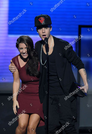 Justin Bieber accepts the award for artist of the year as he embraces his mom Pattie Malette at the 40th Anniversary American Music Awards, in Los Angeles
