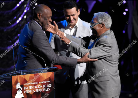 Johnny Ventura, left, presents a Lifetime Achievement award to Rafael Ithier, right, as Victor Manuelle looks on at the Lifetime Achievement and Trustees Awards presentation at the Ka Theater in the MGM Grand Hotel, in Las Vegas