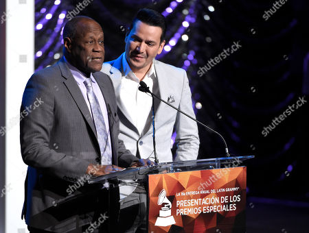 Johnny Ventura, left, and Victor Manuelle present an award at the Lifetime Achievement and Trustees Awards presentation at the Ka Theater in the MGM Grand Hotel, in Las Vegas