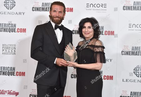 Bradley Cooper, left, poses with Sid Grauman award honoree Sue Kroll at the 30th annual American Cinematheque Award Honoring Ridley Scott at the Beverly Hilton Hotel, in Beverly Hills, Calif