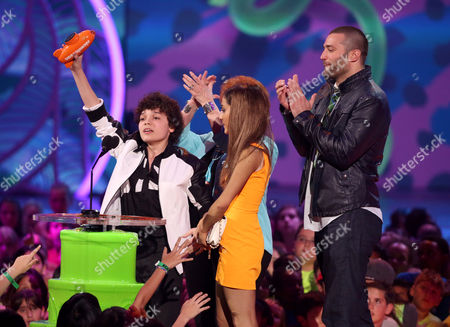 From left, Cameron Ocasio, Ariana Grande, and Zoran Korach accept the award for favorite TV show for Sam & Cat at the 27th annual Kids' Choice Awards at the Galen Center, in Los Angeles
