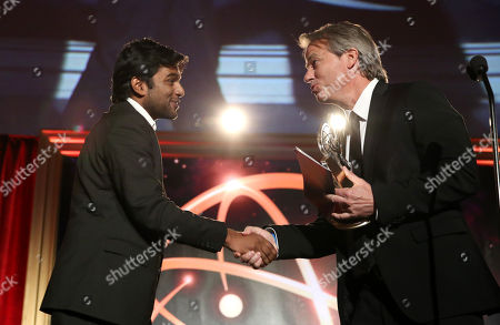"""Graham Yost presents Shubhashish Bhutiani, left, of School of Visual Arts with the Directing Award for """"Kush"""" at the 35th College Television Awards, presented by the Television Academy Foundation at The Leonard H. Goldenson Theatre in the NoHo Arts District, in Los Angeles"""