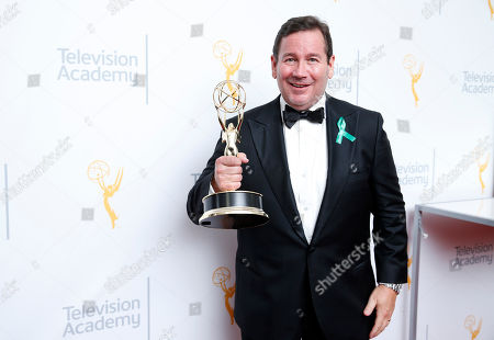 """David Nutter poses with his award for outstanding director for """"Game Of Thrones"""" at the 67th Primetime Emmy Awards, at the Microsoft Theater in Los Angeles"""