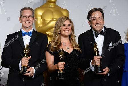 From Left, Chris Buck, Jennifer Lee, and Peter Del Vecho pose in the press room with the award for Best animated feature film of the year during the Oscars at the Dolby Theatre, in Los Angeles