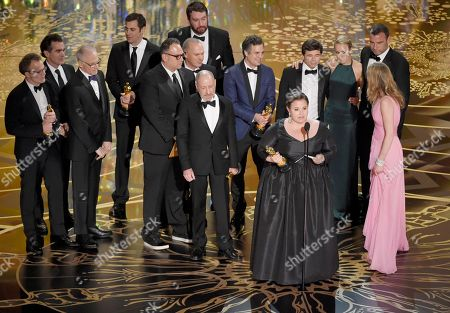 """Nicole Rocklin, foreground at podium, and the cast and crew, from left, director Tom McCarthy, actor Brian d'Arcy James, abuse survivor Phil Saviano, screenwriter Josh Singer, Michael Sugar, Michael Keaton, Steve Golin, Mark Ruffalo, Boston Globe investigative reporter Michael Rezendes, Rachel McAdams, Liev Schreiber, and Blye Pagon Faust accept the award for best picture for """"Spotlight,""""at the Oscars, at the Dolby Theatre in Los Angeles. Man at background center is unidentified"""