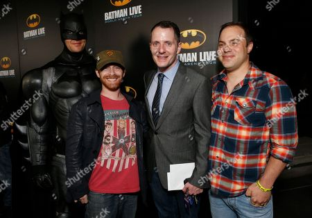 Seth Green, left, Allan Heinberg, writer of Batman Live, and Geoff Johns Chief Officer of DC Comics pose with Batman at the L.A. Batman Live Premiere, at STAPLES Center in Los Angeles