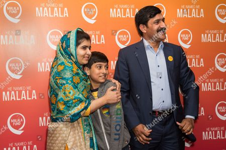 From left, Malala Yousafzai, Atal Khan Yousafzai and Ziauddin Yousafzai pose for photographers upon arrival at the screening of the film 'He Named Me Malala' in London