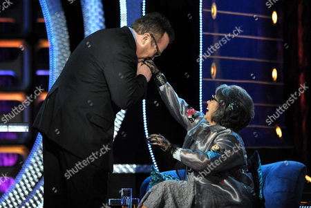 "Stock Photo of Tom Arnold, left, kisses the hand of Roseanne Barr on stage at the Comedy Central ""Roast of Roseanne"" at the Hollywood Palladium, in Los Angeles"