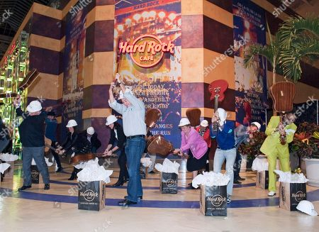 From left; Bloomington Mayor Gene Winstead, President and CEO of Hard Rock International Hamish Dodds, Mall of America owner Tony Ghermezian and musician Morris Day ceremoniously smash guitars to commemorate the Grand Opening of Hard Rock Cafe Mall of America, in Bloomington, Minn