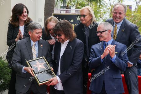 Maureen Schultz, from left, President and CEO of the Hollywood Chamber of Commerce Leron Gubler, Tom Petty, Jeff Lynne, Joe Walsh and Los Angeles City Councilmembers Mitch O'Farrell and Tom LaBonge attend a ceremony honoring Jeff Lynne with a star on The Hollywood Walk of Fame, in Los Angeles