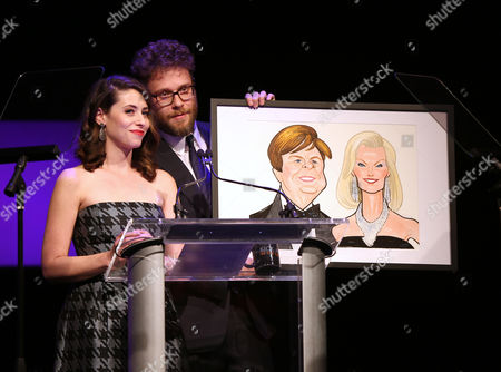 """Lauren Miller and Seth Rogen display a caricature of Peter Grad and Laurie Burrows Grad at the 24th annual Alzheimer's Association """"A Night at Sardi's"""" at the Beverly Hilton hotel, in Beverly Hills, Calif"""