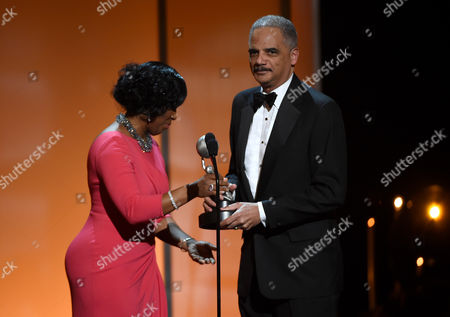 NAACP chairman Roslyn M. Brock, left, presents U.S. Attorney General Eric Holder with the Chairman's Award on stage at the 46th NAACP Image Awards at the Pasadena Civic Auditorium, in Pasadena, Calif