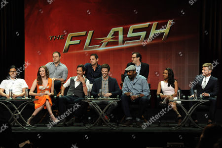 From left, front, Carlos Valdes, Danielle Panabaker, Tom Cavanagh, Grant Gustin, Jesse L. Martin, Candice Patton and Rick Cosnett; rear, Geoff Johns, Chief Creative Officer, DC Entertainment, Executive Producer Greg Berlanti, and Executive Producer Andrew Kreisberg, speak on stage during 'The Flash' panel at the The CW 2014 Summer TCA held at the Beverly Hilton Hotel, in Beverly Hills, Calif