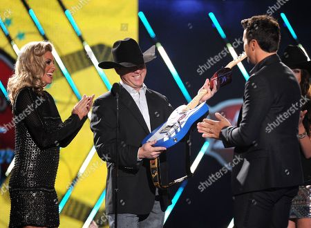 Luke Bryan, right, accepts the male artist of the year award from Shada Brazile, left, and Trevor Brazile onstage at the American Country Awards at the Mandalay Bay Resort & Casino, in Las Vegas, Nev
